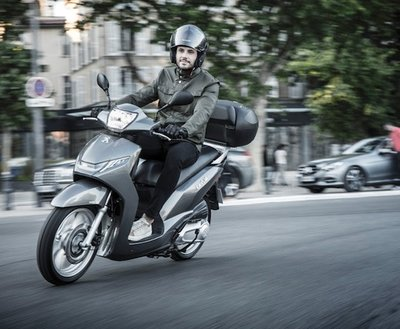 man-riding-peugeot-scooter image