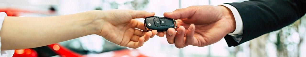 Woman being handed over the keys to her new vehicle