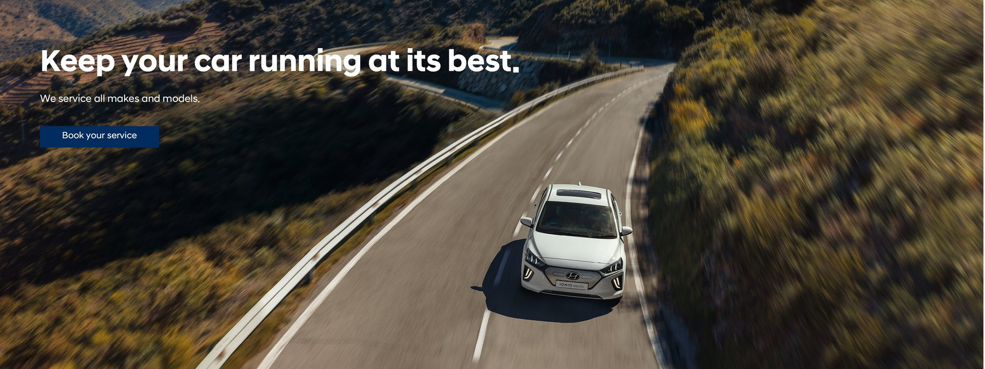 Hyundai car driving on a long and winding road through a green landscape