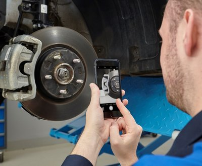 Mechanic holding smart phone to take picture of a wheel in the workshop image