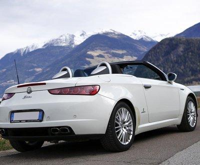 White Alfa Romeo convertible in a mountain landscape image