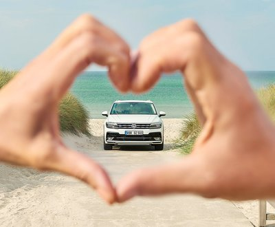 Volkswagen on the beach seen through a pair of hands forming a heart image