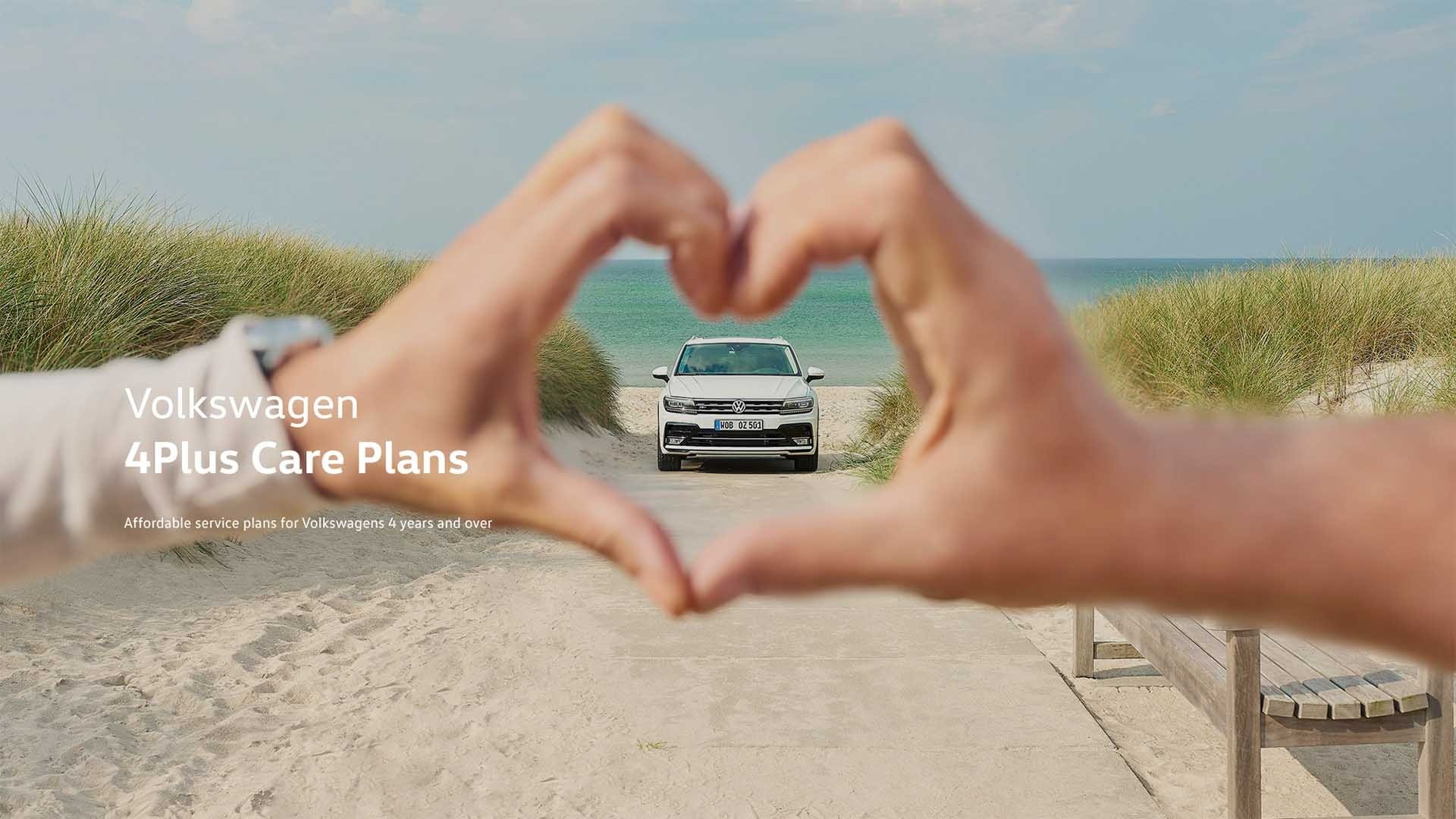 A Volkswagen on the beach as seen through two hands forming a heart shape