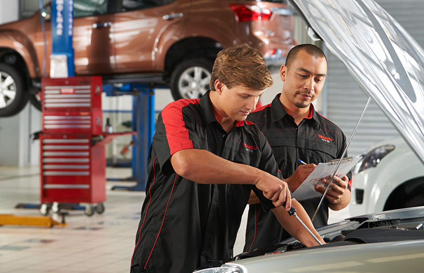 Two Isuzu UTE Service Plus technicians service the engine of an Isuzu Ute