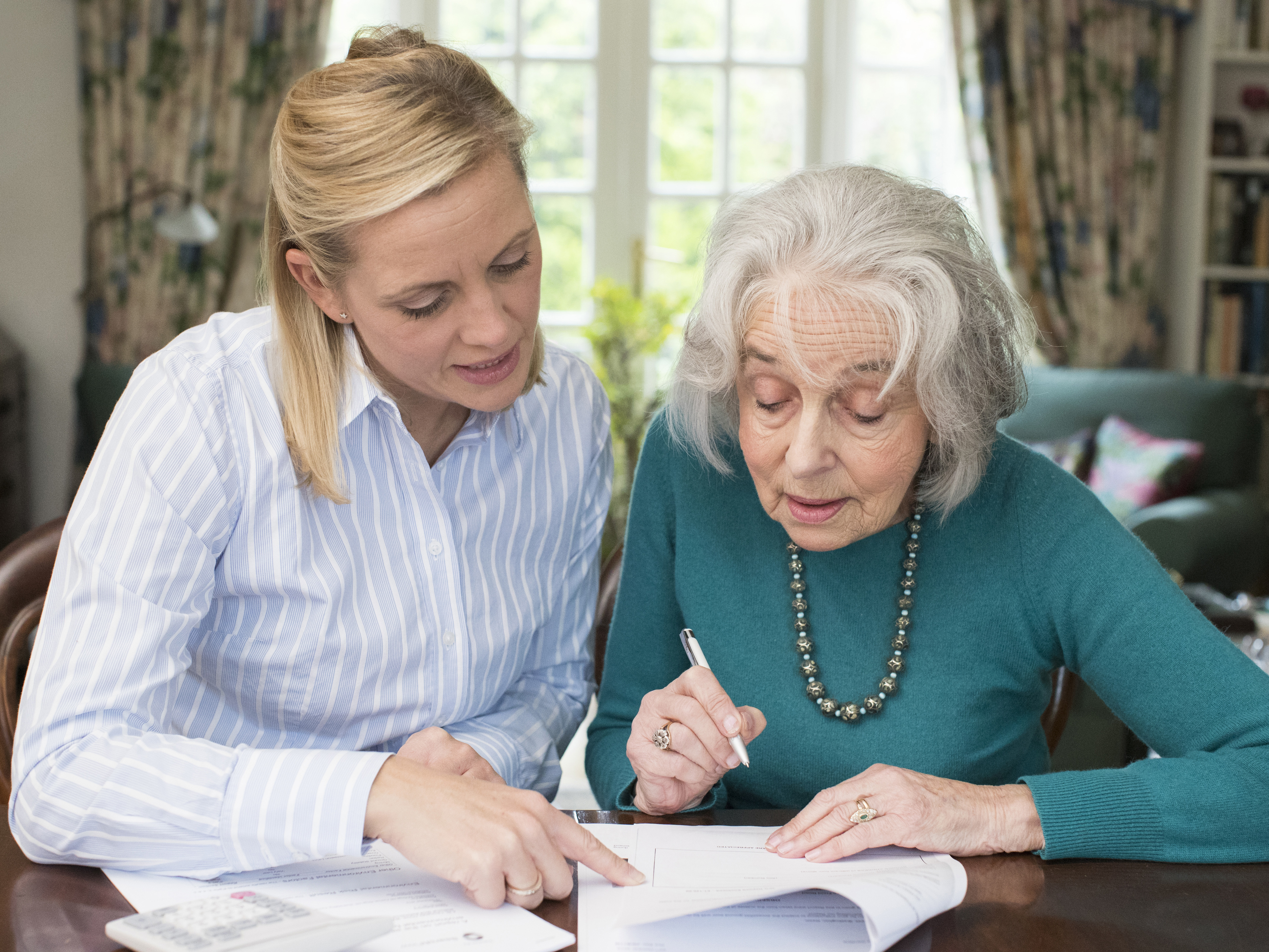 Woman helping older woman with her documents.