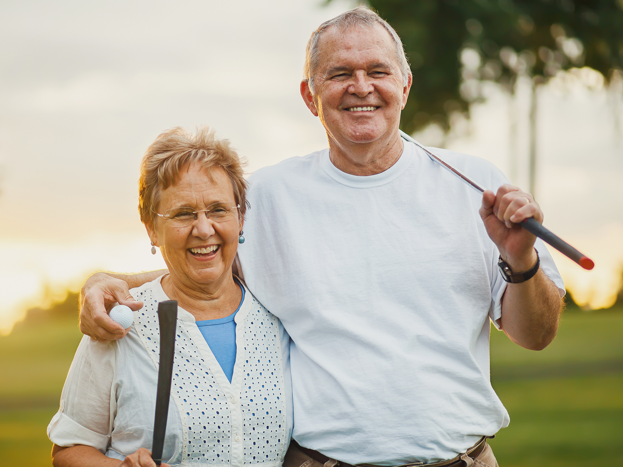 Happy retired couple playing golf