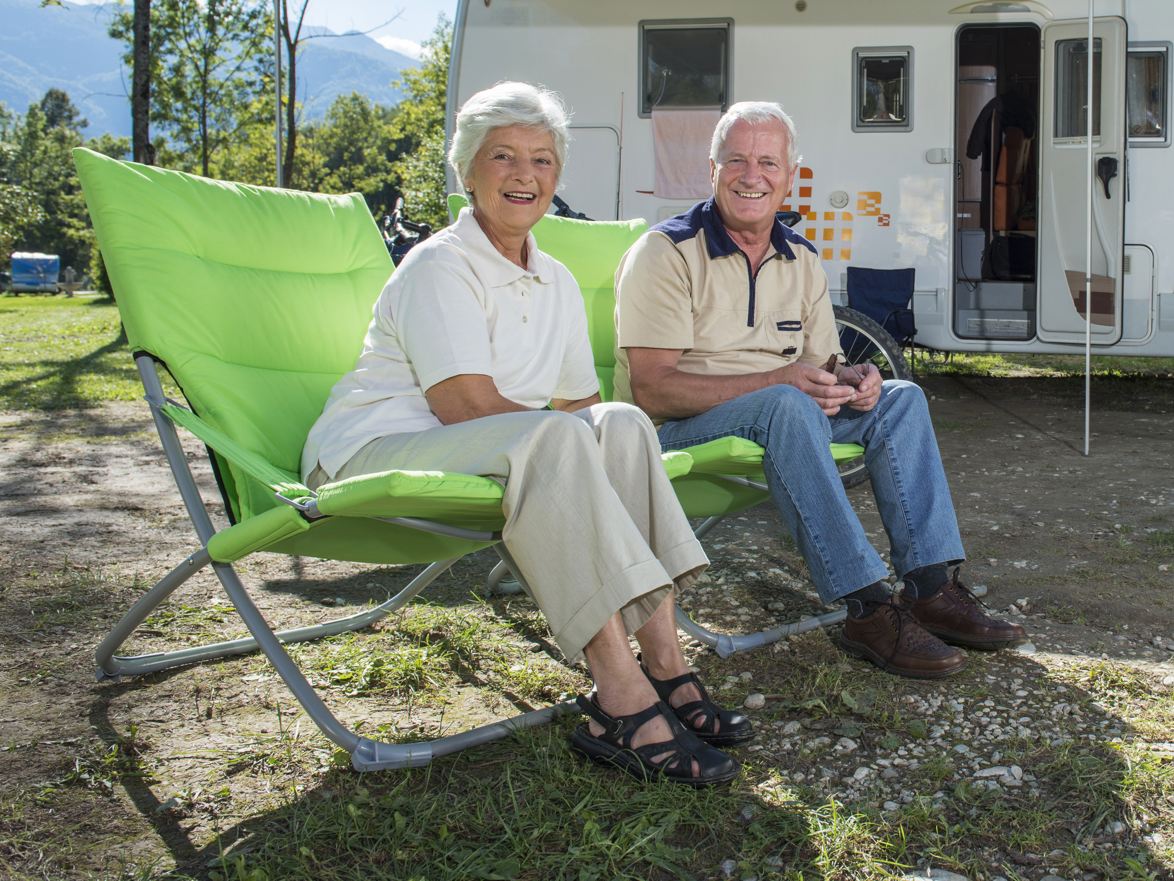 Older couple sitting outside near their campervan