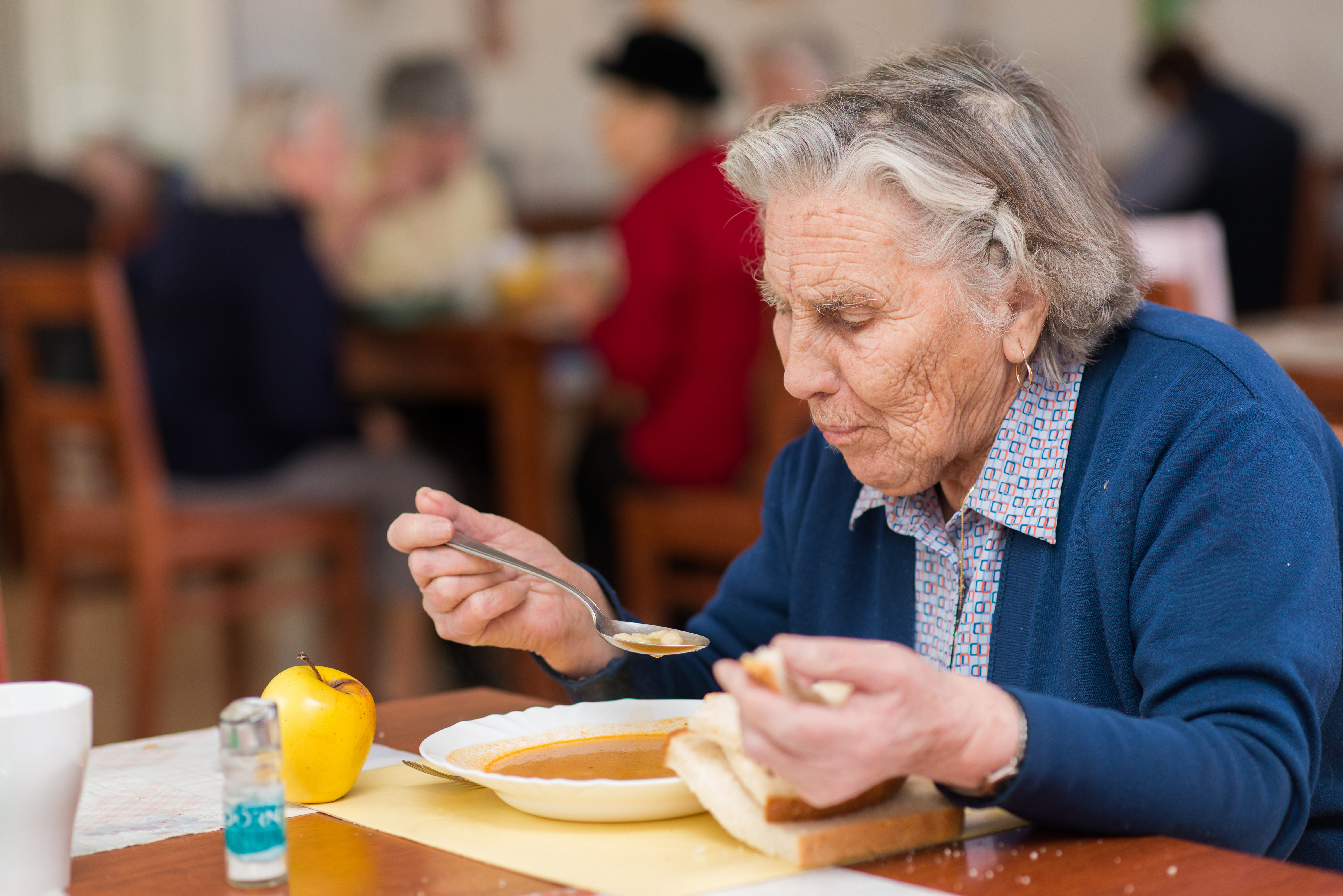 Older woman in aged care having soup.