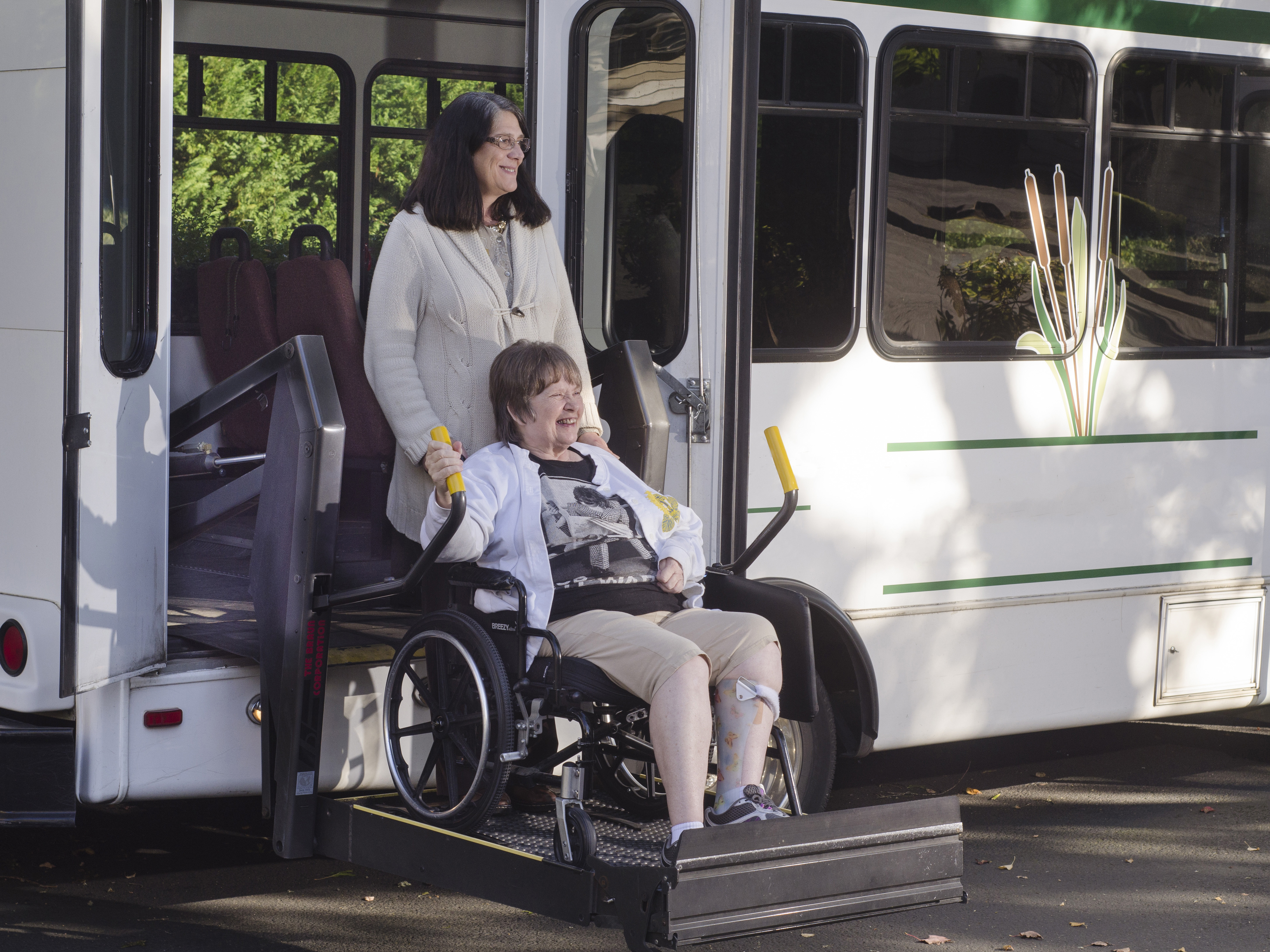 Older woman receiving assistance getting off community transport