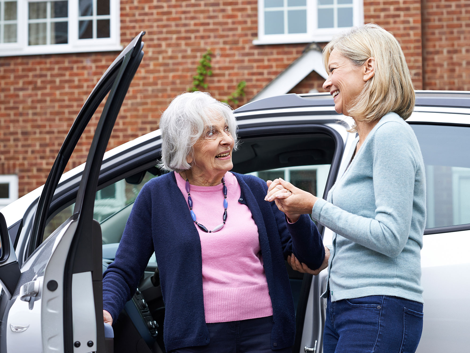 A carer helping an older woman get out the car.