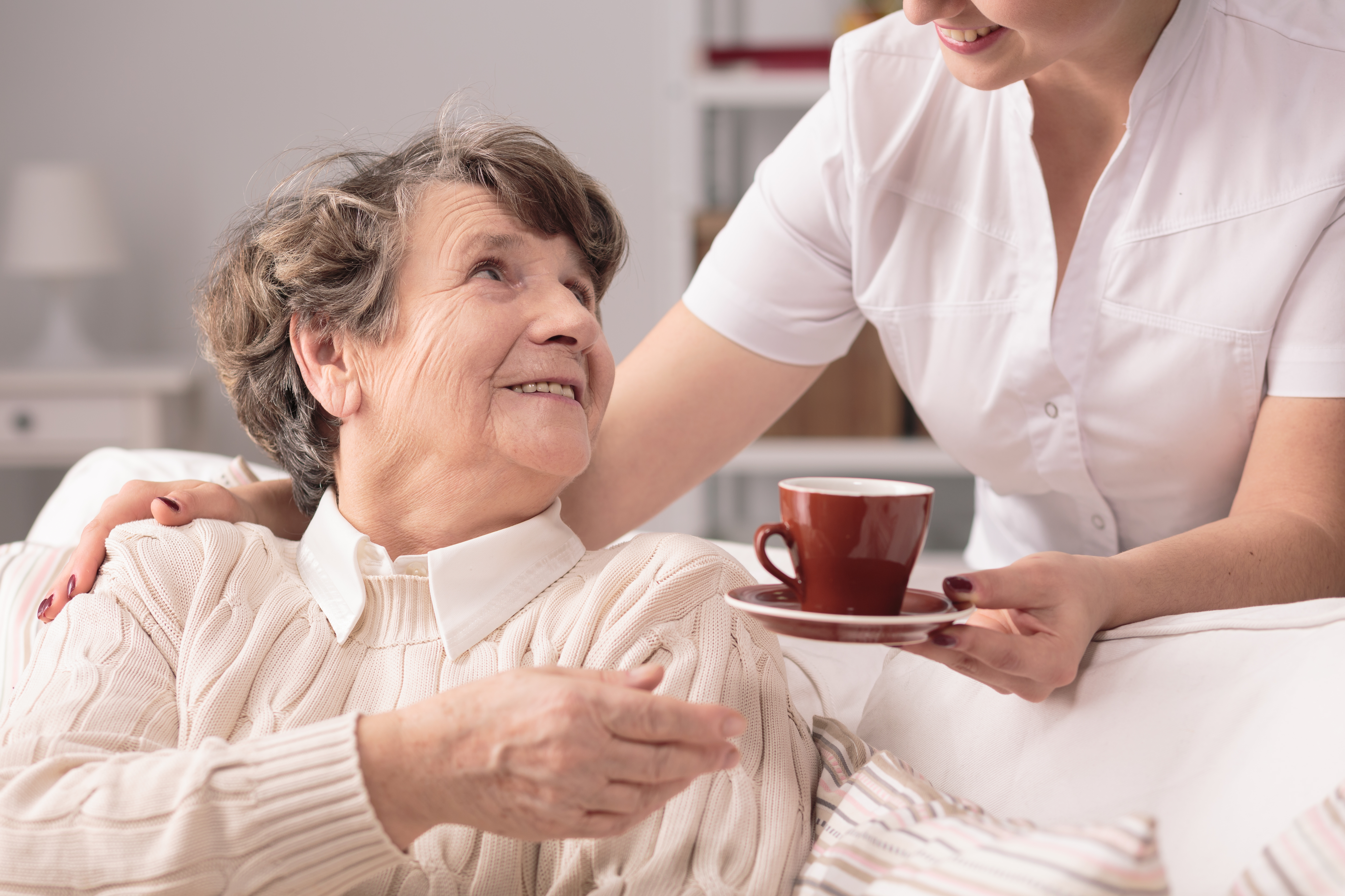 Older woman accepting tea from a carer at her home.
