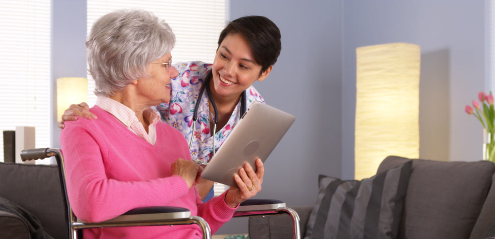 A woman talking with an aged carer in a nice home