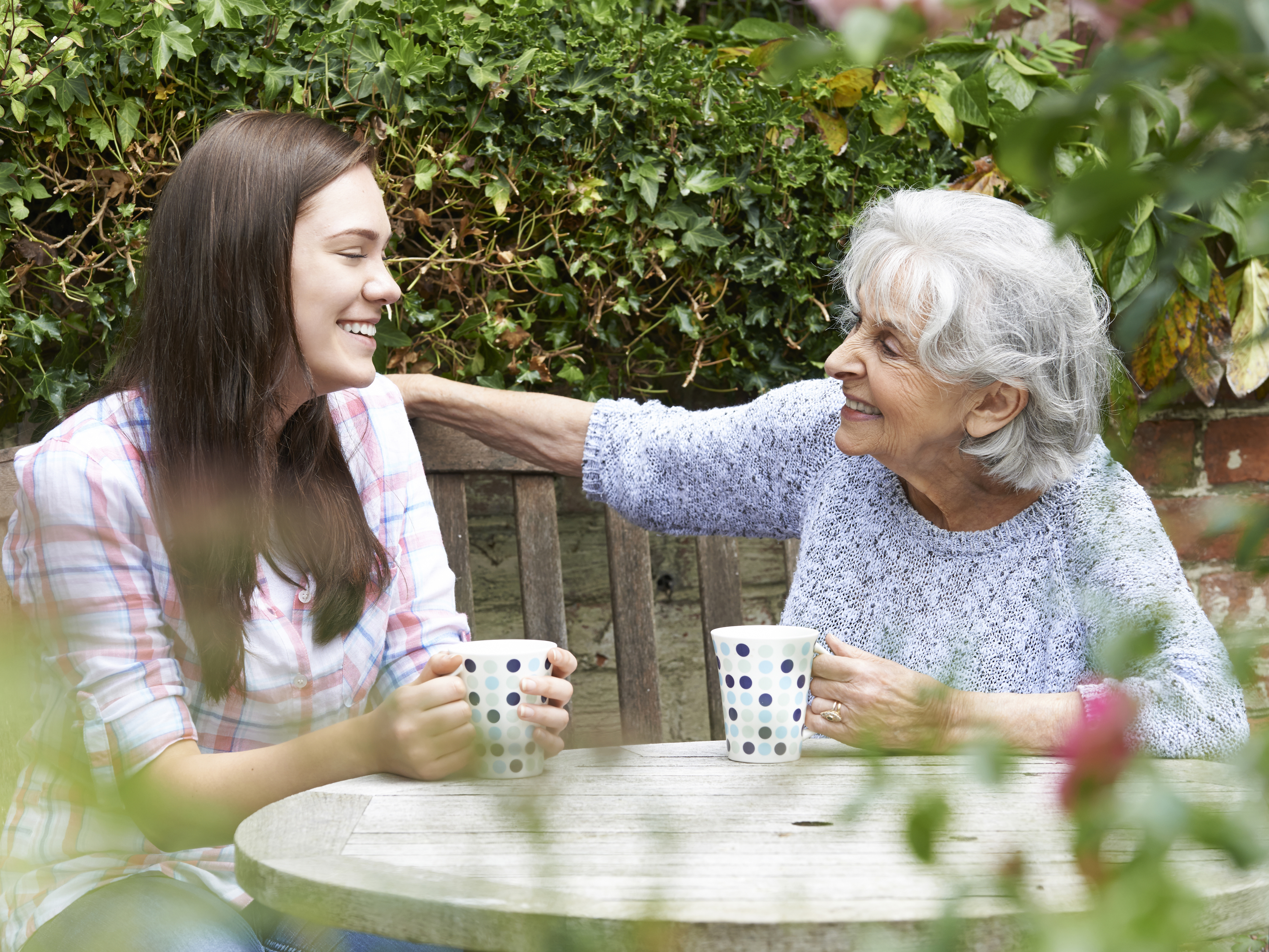 An older woman having a cuppa with a person.