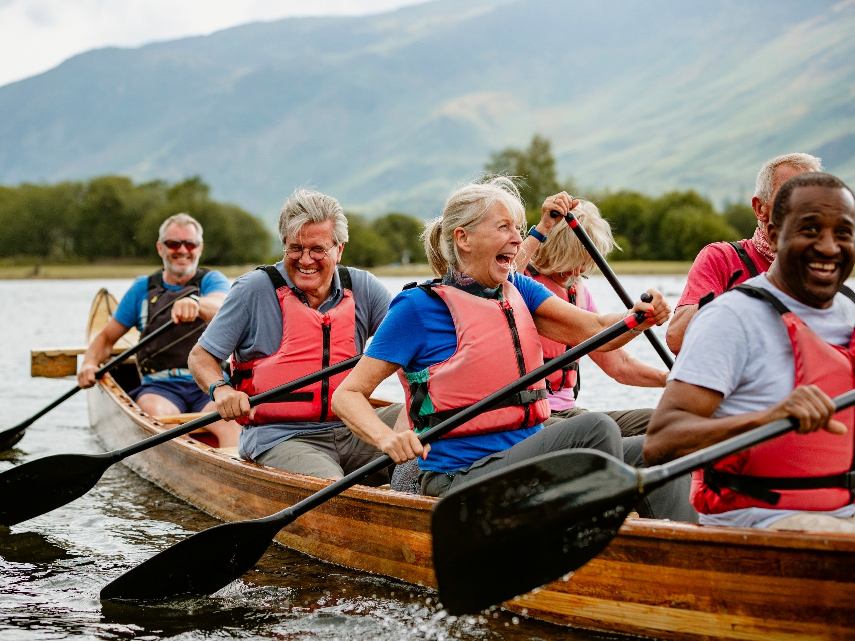 Older group of people paddling a boat