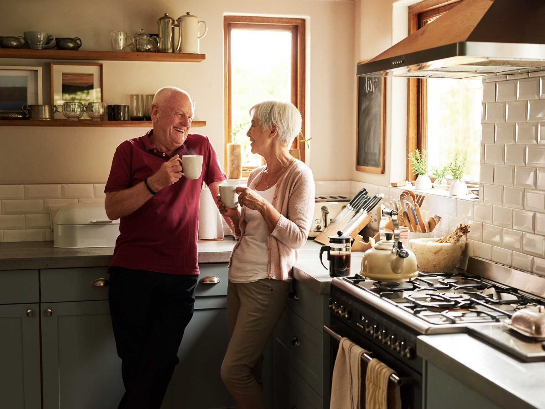 Soon to be retirees relaxing together in their kitchen with their morning coffee.