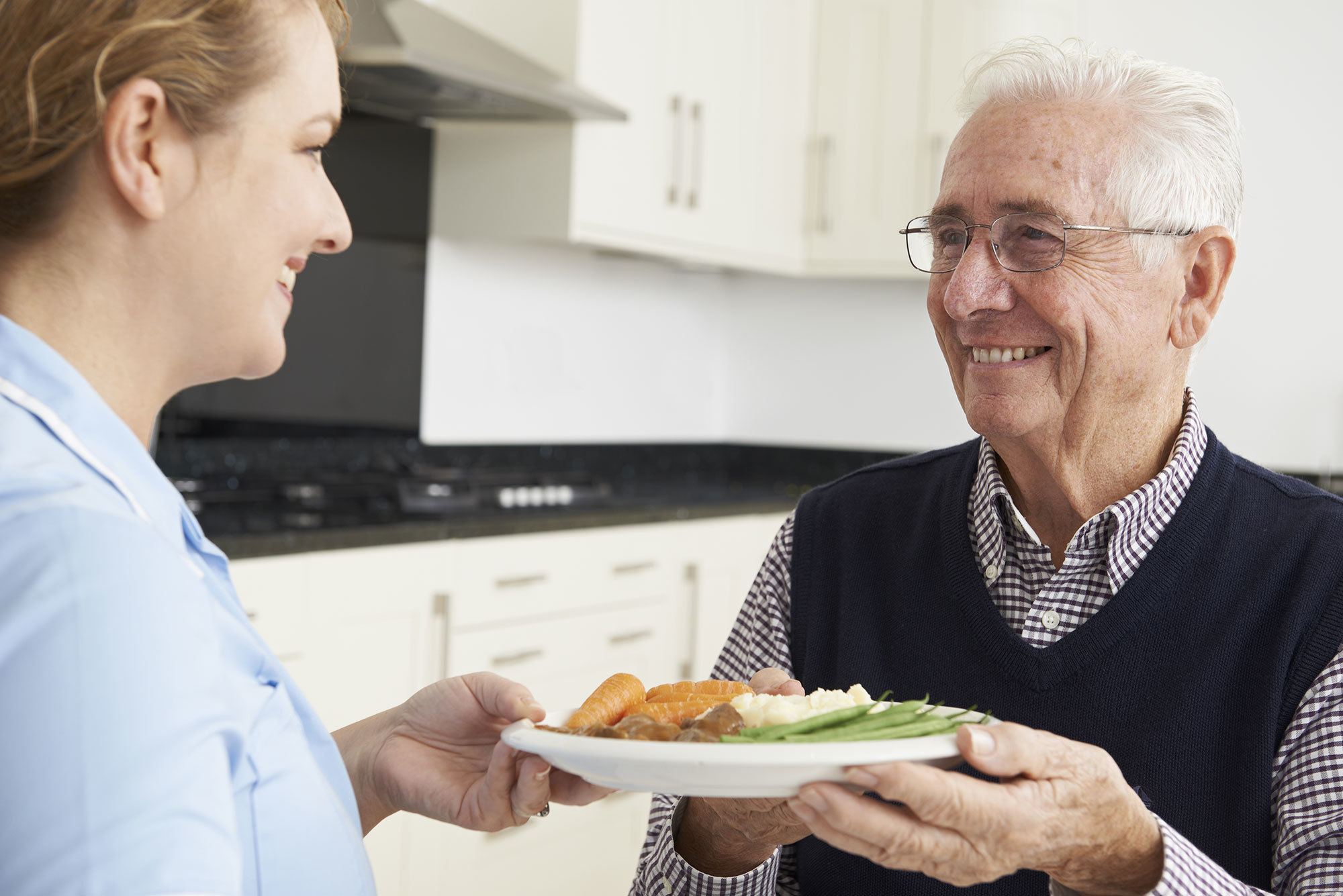 Older man receiving help making his dinner from a carer