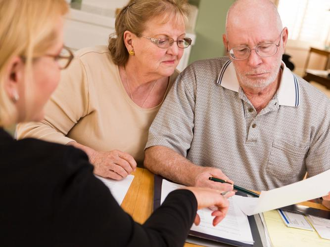 Older couple sorting out their finances with a financial planner