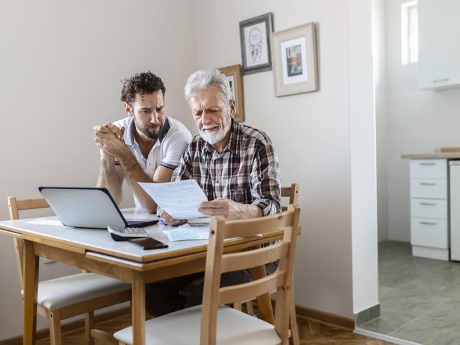 Older man going through his Advance Care Directive documents with his son.