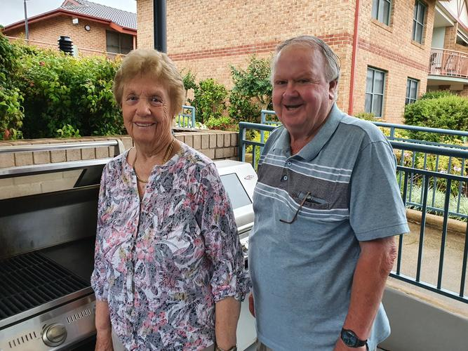 Two older retirees at their retirement village barbecue spot.
