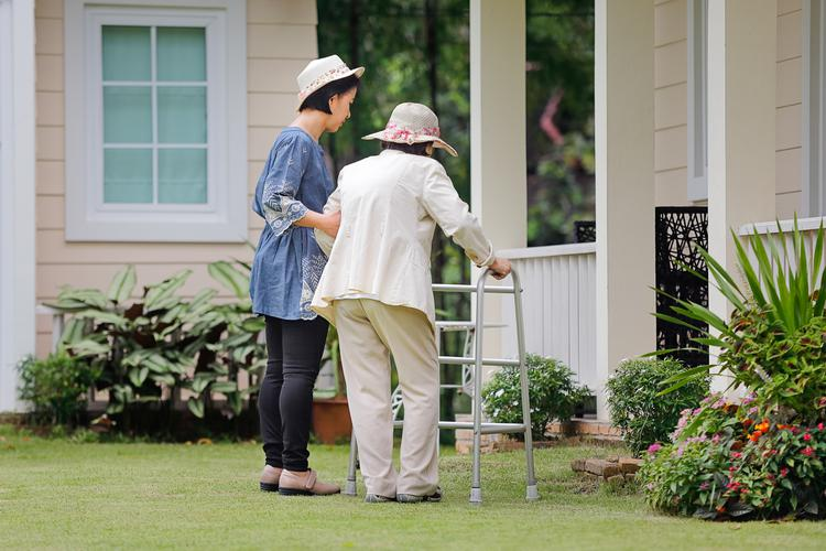 Assisting elderly lady with walking frame