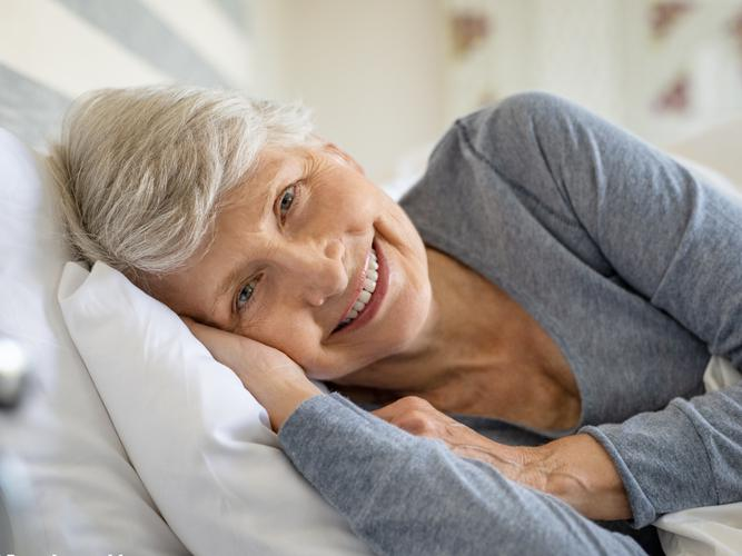 Older woman about to go to sleep in bed