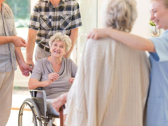 Woman catching up with other residents in aged care