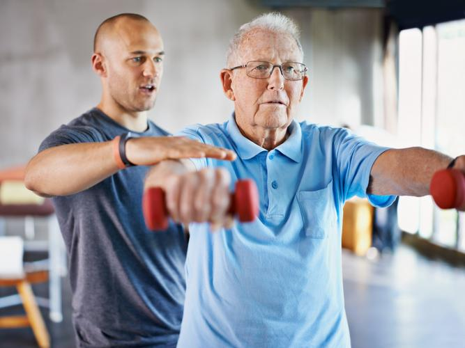 A physiotherapist is helping an older man exercise