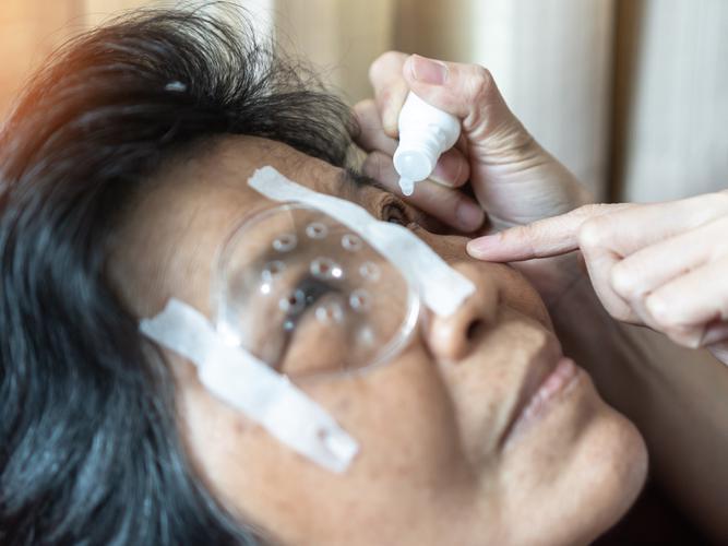 Woman receiving eye drops for her AMD.