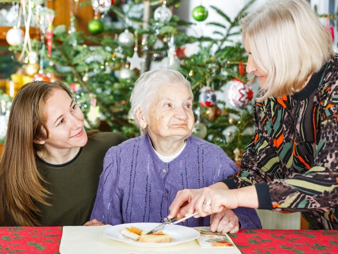 Family assisting older woman with dementia
