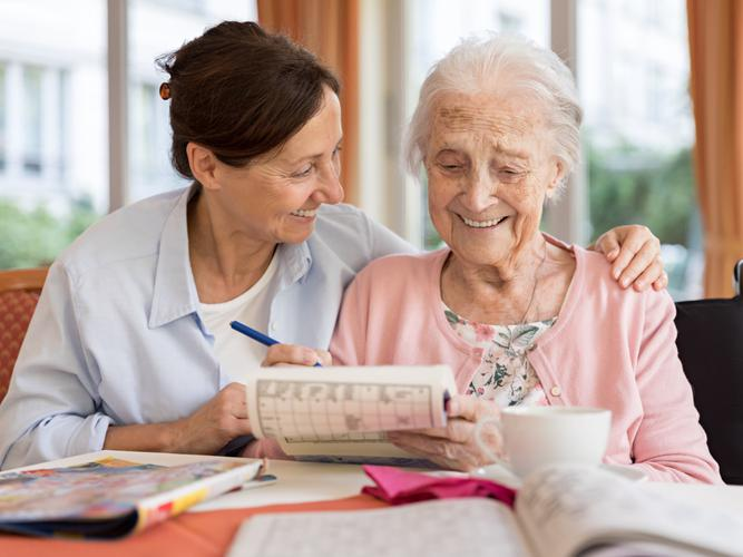 Older woman receiving help from her care giver
