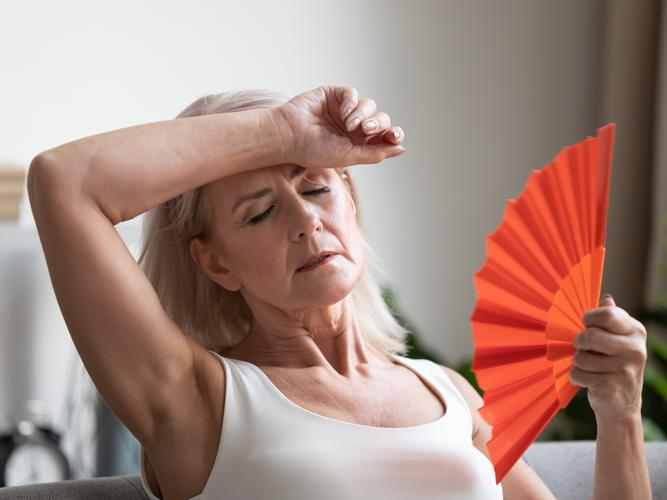 Women is not coping during hot weather and is cooling down using a fan
