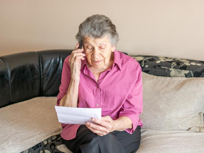 Older woman waiting on the phone.