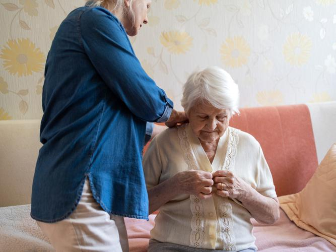 Older woman receives help at home from a carer
