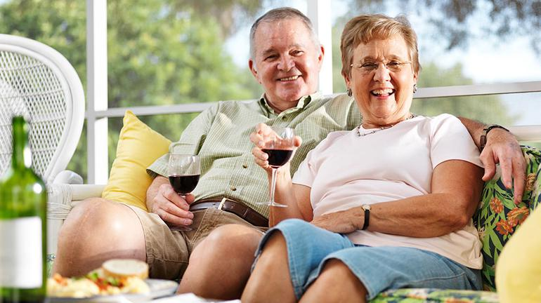 Elderly couple enjoying food on a couch
