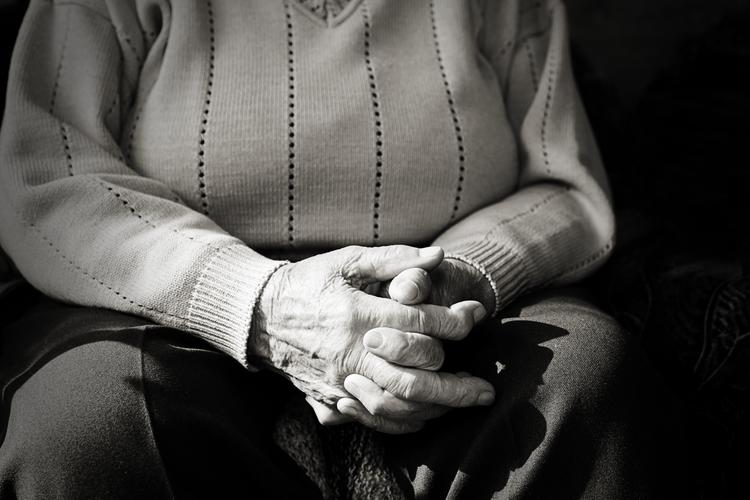 Older person in aged care sitting clapsing hands in lap