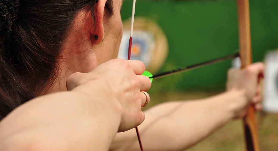 A person holding a drawn bow and arrow
