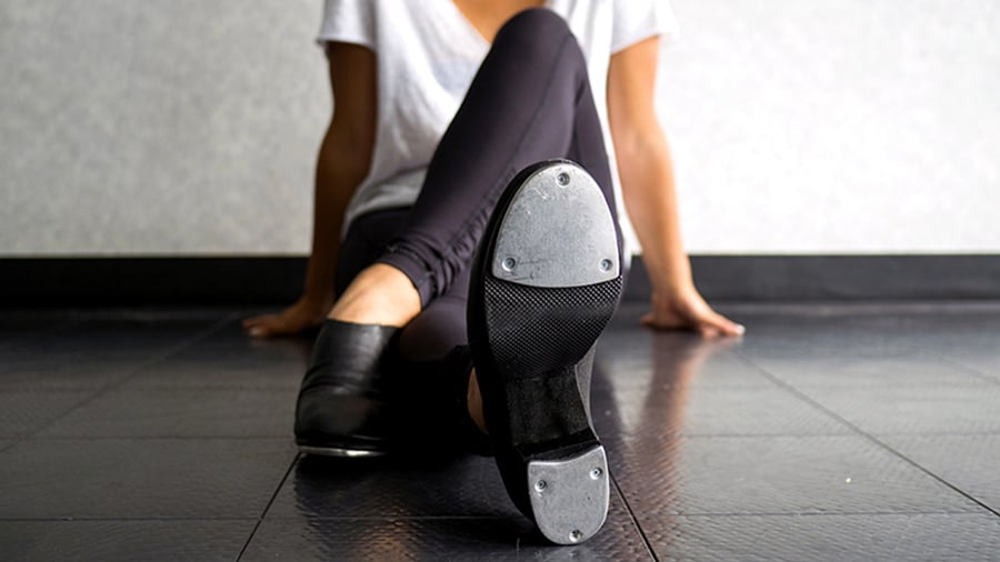 Woman sitting on the floor wearing tap shoes