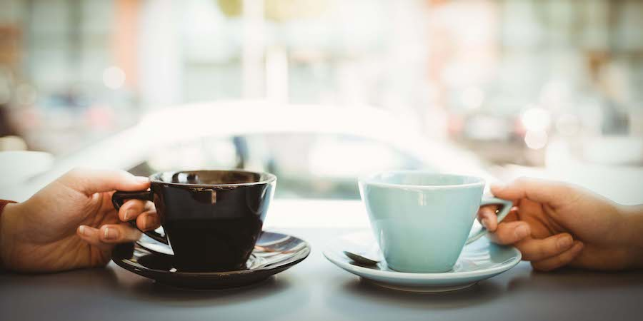 Two hands holding coffee cups on a café table