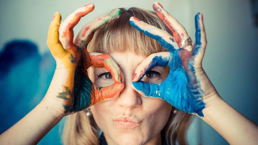 Blonde painter in her studio with her hands around her eyes