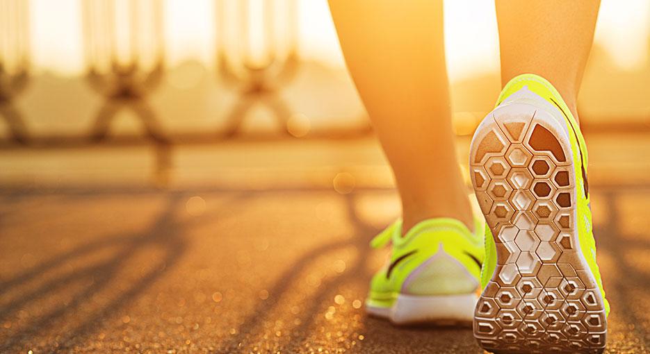 A person wearing fluoro yellow trainers walking on asphalt