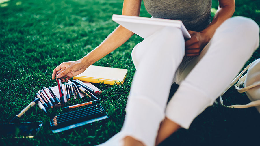 Woman sketching with markers while sitting outside on grass
