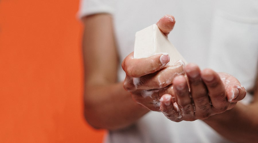 A person scrubbing their hands with a bar of soap