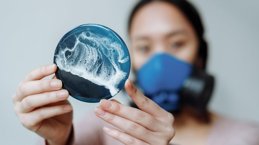 Woman holds a piece of wave-patterned resin art