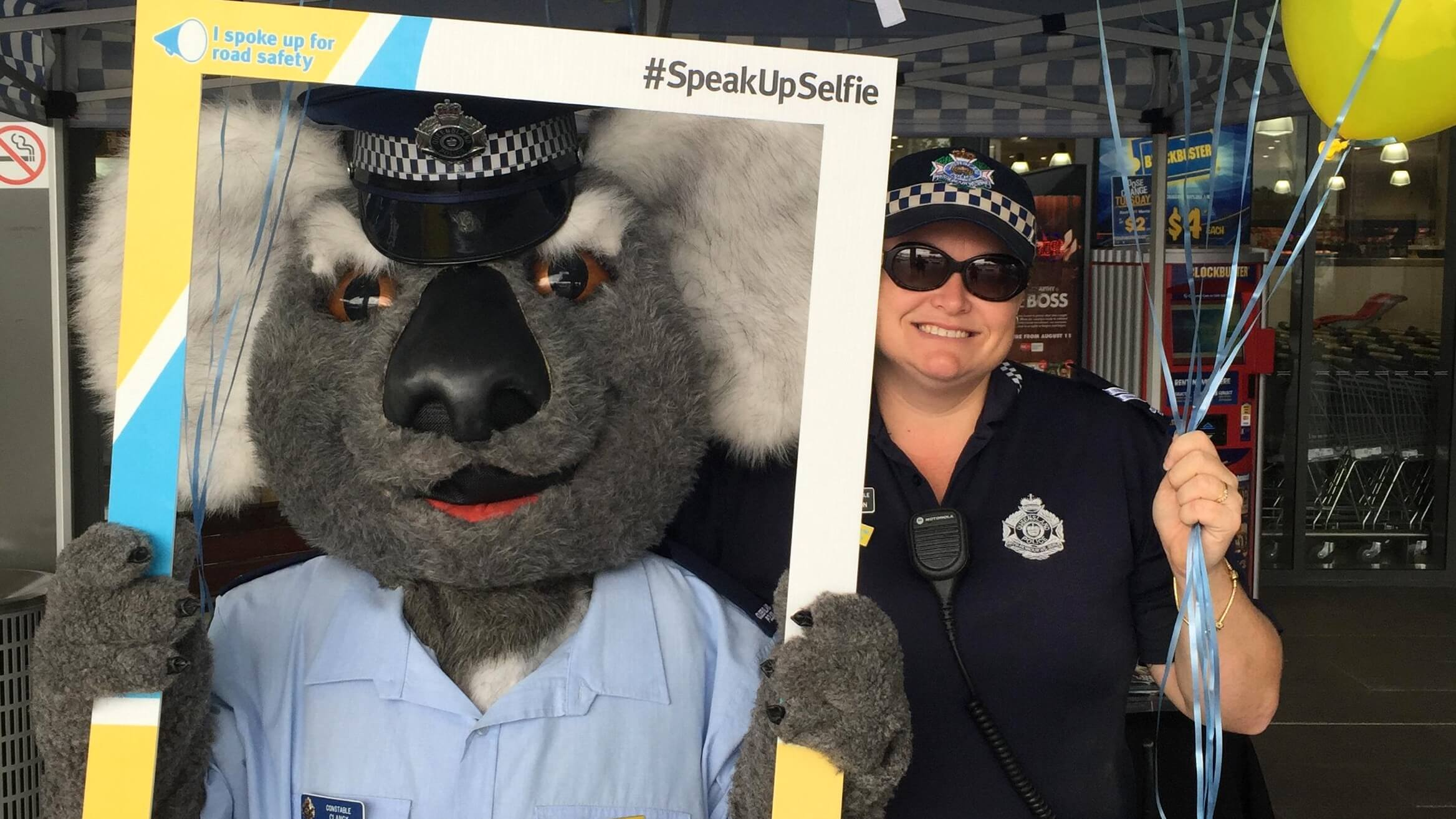 Police officer and a mascot Koala posing with a #SpeakUpSelfie frame at a Road Safety Week event