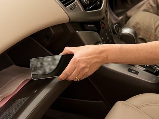 Driver putting phone in glovebox