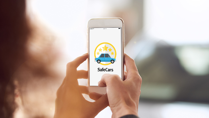 Lady holding up mobile phone with SafeCars app installed and open