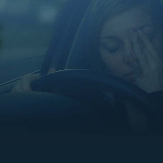 Woman rubbing her eyes behind the wheel fo a car