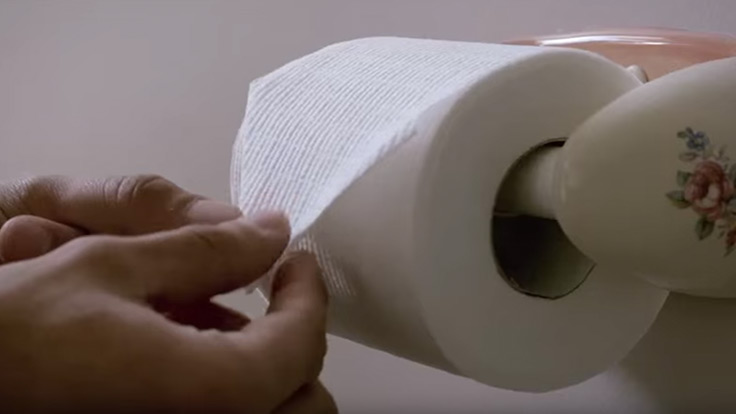 Close up view of man folding the tips in on the end of a roll of toilet paper