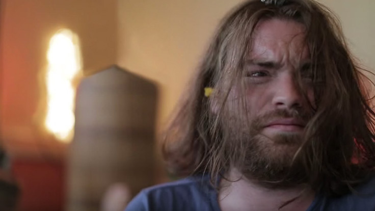 Man with scruffy long hair and beard who looks like he has just woken up from a wild night