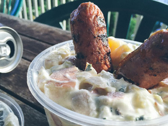 A small bowl of potato salad with two sausages stuck in it sitting on an outdoor table